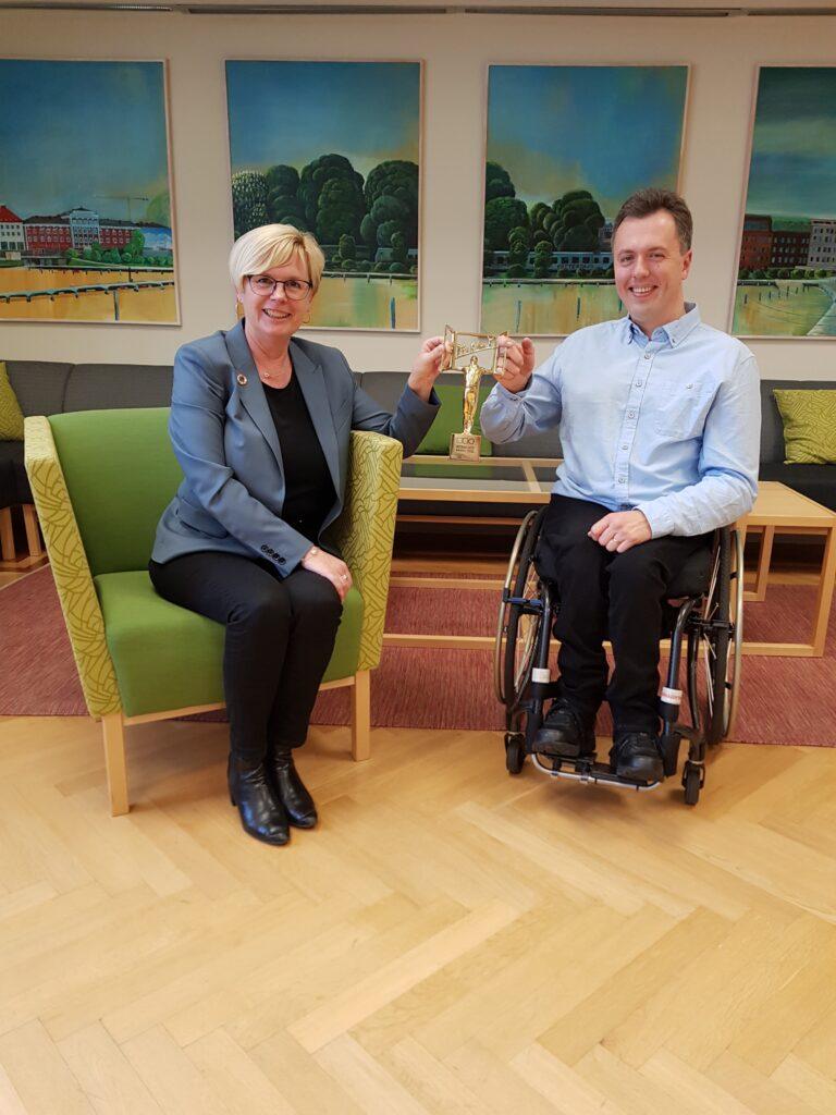 Bild på kommunalrådet Ann-Marie Nilsson och Funktionsrätts Johan Steirud. Sitter ner och håller båda i priset mellan sig.